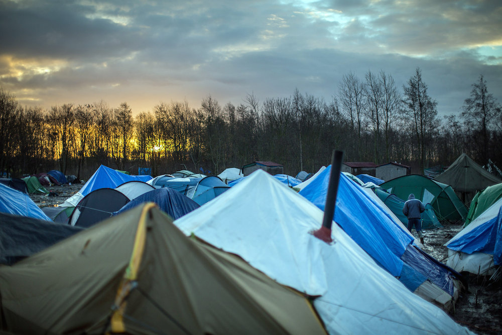 "The sun rises as awful muddy conditions can be seen at the Grand-Synthe migrant camp in Dunkirk, France, caused by several days of torrential rain. 05 January 2016. These harrowing pictures show the desperate conditions in a French refugee camp - which has become become a mudbath due to torrential rain. See swns story SWDUNKIRK. The Grand-Synthe settlement in Dunkirk is home to around 2,500 migrants who are living in conditions so squalid that aid workers say it is on the brink of a sanitation crisis. It is described as ""far worse than the Calais jungle"" but has largely gone unnoticed until now. Disturbing images show young children wading knee-deep through thick mud while their families huddle around fires, surrounded by ever-growing piles of rubbish. In some places, mounds of sodden clothing, mud-soaked duvets and shoes swallowed by the swamp sit next to polluted streams and marquees selling food. Elsewhere, metal sheets form makeshift paths between groups of tents in the flooded field, which has been battered by constant rain in recent weeks. Grande-Synthe camp has only two drinking water points and 26 toilets, which is roughly one per 100 people - five times fewer than the bare minimum in other refugee camps. The occupants, who are mostly Iraqi Kurds with some Syrians and Persians, live in squalid marshland conditions which are rife with disease and infested by rats. There are no healthcare facilities whatsoever, though doctors from Médecins Sans Frontières‎ (MSF) visit the camp a few times a week to treat the sick."