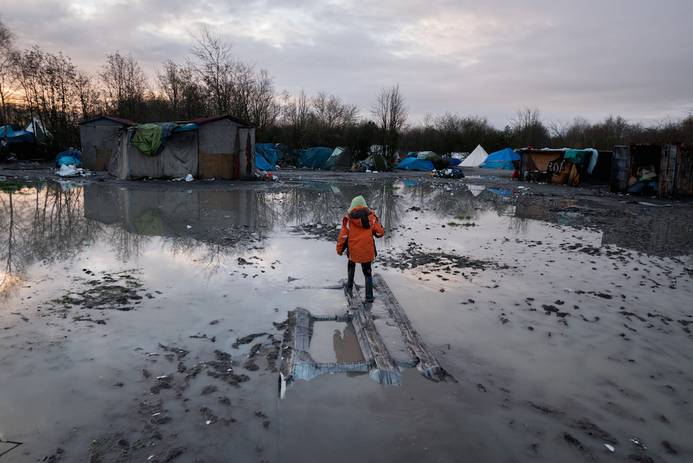 """A young migrant boy walks through awful muddy conditions at the Grand-Synthe migrant camp in Dunkirk, France, caused by several days of torrential rain. 05 January 2016. These harrowing pictures show the desperate conditions in a French refugee camp - which has become become a mudbath due to torrential rain. See swns story SWDUNKIRK. The Grand-Synthe settlement in Dunkirk is home to around 2,500 migrants who are living in conditions so squalid that aid workers say it is on the brink of a sanitation crisis. It is described as """"far worse than the Calais jungle"""" but has largely gone unnoticed until now. Disturbing images show young children wading knee-deep through thick mud while their families huddle around fires, surrounded by ever-growing piles of rubbish. In some places, mounds of sodden clothing, mud-soaked duvets and shoes swallowed by the swamp sit next to polluted streams and marquees selling food. Elsewhere, metal sheets form makeshift paths between groups of tents in the flooded field, which has been battered by constant rain in recent weeks. Grande-Synthe camp has only two drinking water points and 26 toilets, which is roughly one per 100 people - five times fewer than the bare minimum in other refugee camps. The occupants, who are mostly Iraqi Kurds with some Syrians and Persians, live in squalid marshland conditions which are rife with disease and infested by rats. There are no healthcare facilities whatsoever, though doctors from Médecins Sans Frontières (MSF) visit the camp a few times a week to treat the sick."""