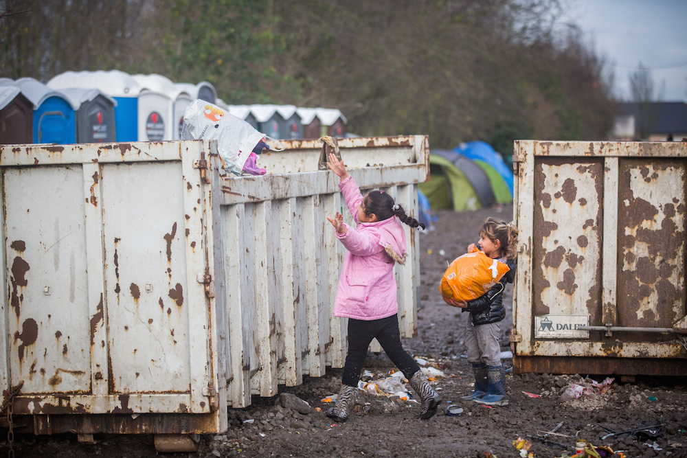 "Children through rubbish in the skips as awful muddy conditions can be seen at the Grand-Synthe migrant camp in Dunkirk, France, caused by several days of torrential rain. 05 January 2016. These harrowing pictures show the desperate conditions in a French refugee camp - which has become become a mudbath due to torrential rain. See swns story SWDUNKIRK. The Grand-Synthe settlement in Dunkirk is home to around 2,500 migrants who are living in conditions so squalid that aid workers say it is on the brink of a sanitation crisis. It is described as ""far worse than the Calais jungle"" but has largely gone unnoticed until now. Disturbing images show young children wading knee-deep through thick mud while their families huddle around fires, surrounded by ever-growing piles of rubbish. In some places, mounds of sodden clothing, mud-soaked duvets and shoes swallowed by the swamp sit next to polluted streams and marquees selling food. Elsewhere, metal sheets form makeshift paths between groups of tents in the flooded field, which has been battered by constant rain in recent weeks. Grande-Synthe camp has only two drinking water points and 26 toilets, which is roughly one per 100 people - five times fewer than the bare minimum in other refugee camps. The occupants, who are mostly Iraqi Kurds with some Syrians and Persians, live in squalid marshland conditions which are rife with disease and infested by rats. There are no healthcare facilities whatsoever, though doctors from Médecins Sans Frontières‎ (MSF) visit the camp a few times a week to treat the sick."