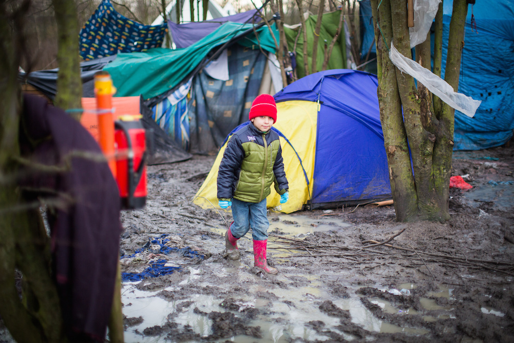 "A young boy walks through awful muddy conditions at the Grand-Synthe migrant camp in Dunkirk, France, caused by several days of torrential rain. 05 January 2016. These harrowing pictures show the desperate conditions in a French refugee camp - which has become become a mudbath due to torrential rain. See swns story SWDUNKIRK. The Grand-Synthe settlement in Dunkirk is home to around 2,500 migrants who are living in conditions so squalid that aid workers say it is on the brink of a sanitation crisis. It is described as ""far worse than the Calais jungle"" but has largely gone unnoticed until now. Disturbing images show young children wading knee-deep through thick mud while their families huddle around fires, surrounded by ever-growing piles of rubbish. In some places, mounds of sodden clothing, mud-soaked duvets and shoes swallowed by the swamp sit next to polluted streams and marquees selling food. Elsewhere, metal sheets form makeshift paths between groups of tents in the flooded field, which has been battered by constant rain in recent weeks. Grande-Synthe camp has only two drinking water points and 26 toilets, which is roughly one per 100 people - five times fewer than the bare minimum in other refugee camps. The occupants, who are mostly Iraqi Kurds with some Syrians and Persians, live in squalid marshland conditions which are rife with disease and infested by rats. There are no healthcare facilities whatsoever, though doctors from Médecins Sans Frontières‎ (MSF) visit the camp a few times a week to treat the sick."