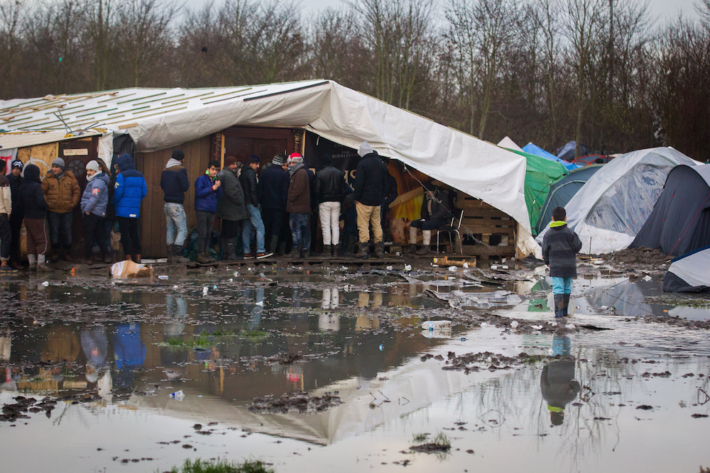 "Migrants wait for the kitchen to be opened as awful muddy conditions can be seen at the Grand-Synthe migrant camp in Dunkirk, France, caused by several days of torrential rain. 05 January 2016. These harrowing pictures show the desperate conditions in a French refugee camp - which has become become a mudbath due to torrential rain. See swns story SWDUNKIRK. The Grand-Synthe settlement in Dunkirk is home to around 2,500 migrants who are living in conditions so squalid that aid workers say it is on the brink of a sanitation crisis. It is described as ""far worse than the Calais jungle"" but has largely gone unnoticed until now. Disturbing images show young children wading knee-deep through thick mud while their families huddle around fires, surrounded by ever-growing piles of rubbish. In some places, mounds of sodden clothing, mud-soaked duvets and shoes swallowed by the swamp sit next to polluted streams and marquees selling food. Elsewhere, metal sheets form makeshift paths between groups of tents in the flooded field, which has been battered by constant rain in recent weeks. Grande-Synthe camp has only two drinking water points and 26 toilets, which is roughly one per 100 people - five times fewer than the bare minimum in other refugee camps. The occupants, who are mostly Iraqi Kurds with some Syrians and Persians, live in squalid marshland conditions which are rife with disease and infested by rats. There are no healthcare facilities whatsoever, though doctors from Médecins Sans Frontières‎ (MSF) visit the camp a few times a week to treat the sick."