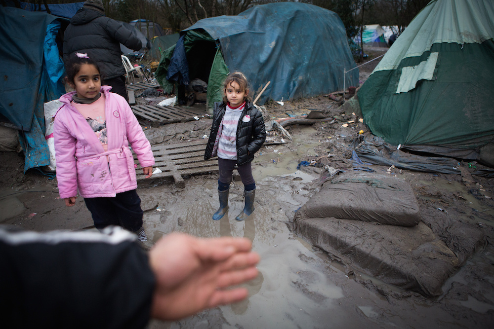 "Sisters Havin, 6, and Hana Ttahsin, 4, from Kurdistan stand in awful muddy conditions at the Grand-Synthe migrant camp in Dunkirk, France. 04 January 2016. These harrowing pictures show the desperate conditions in a French refugee camp - which has become become a mudbath due to torrential rain. See swns story SWDUNKIRK. The Grand-Synthe settlement in Dunkirk is home to around 2,500 migrants who are living in conditions so squalid that aid workers say it is on the brink of a sanitation crisis. It is described as ""far worse than the Calais jungle"" but has largely gone unnoticed until now. Disturbing images show young children wading knee-deep through thick mud while their families huddle around fires, surrounded by ever-growing piles of rubbish. In some places, mounds of sodden clothing, mud-soaked duvets and shoes swallowed by the swamp sit next to polluted streams and marquees selling food. Elsewhere, metal sheets form makeshift paths between groups of tents in the flooded field, which has been battered by constant rain in recent weeks. Grande-Synthe camp has only two drinking water points and 26 toilets, which is roughly one per 100 people - five times fewer than the bare minimum in other refugee camps. The occupants, who are mostly Iraqi Kurds with some Syrians and Persians, live in squalid marshland conditions which are rife with disease and infested by rats. There are no healthcare facilities whatsoever, though doctors from Médecins Sans Frontières‎ (MSF) visit the camp a few times a week to treat the sick."