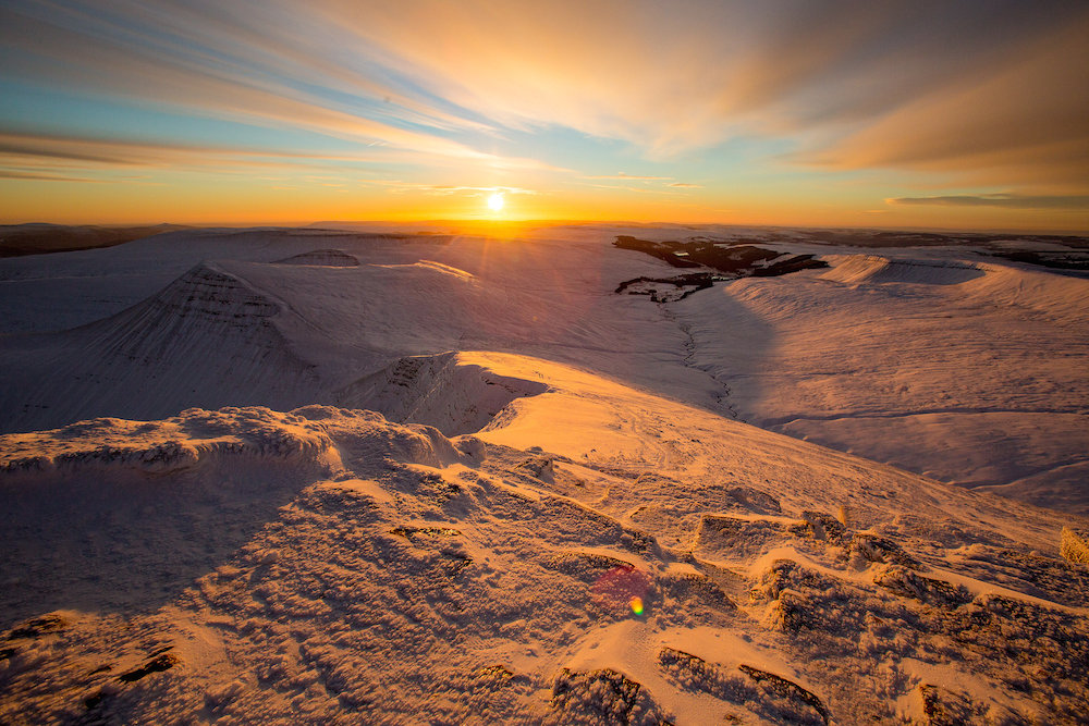 The sun bursts over the horizon from Pen Y Fan, South Wales, the highest point in the South of the UK, as much of the higher ground in the country is covered in snow. January 16, 2016.