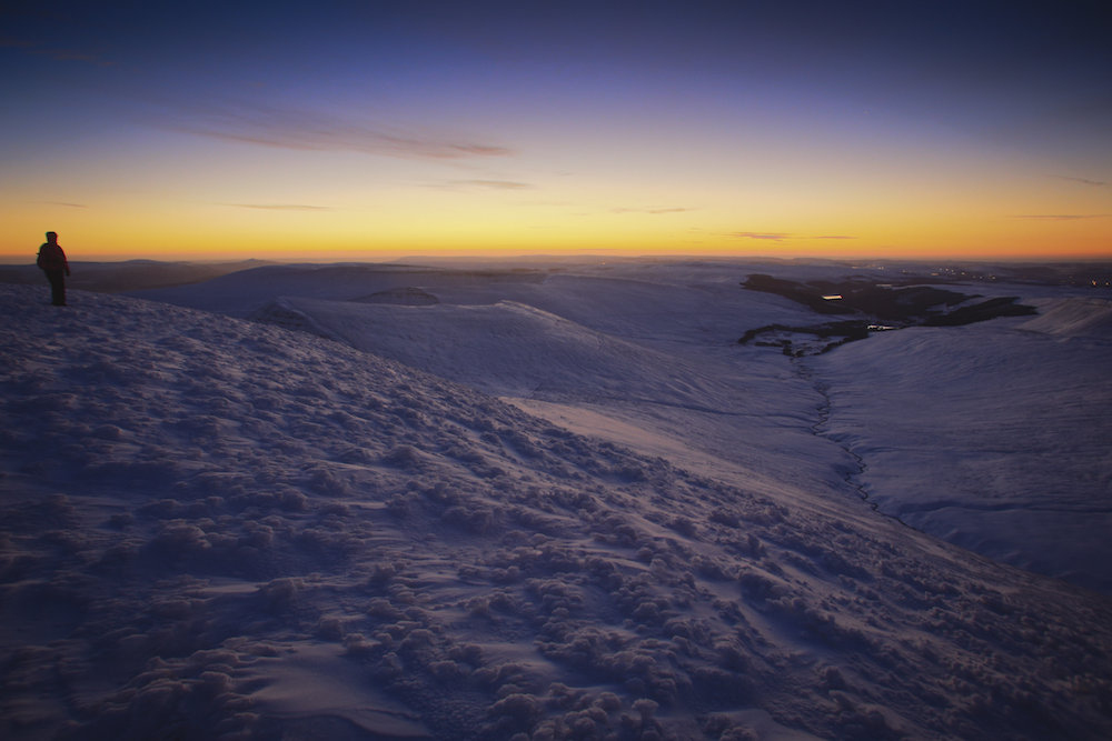 Early risers watch as the warm glow of the rising sun lights the cold slopes of snow covered Pen y Fan, January 16 2016. At 886 metres Pen y Fan is the highest peak in south Wales, situated in the Brecon Beacons National Park.