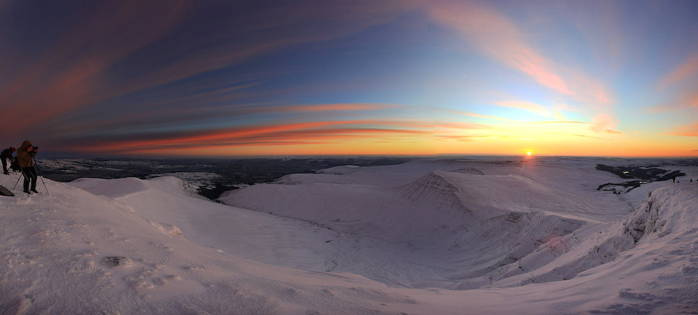Photo montage made from several pictures - Early risers watch as the warm glow of the rising sun lights the cold slopes of snow covered Pen y Fan, January 16 2016. At 886 metres Pen y Fan is the highest peak in south Wales, situated in the Brecon Beacons National Park.