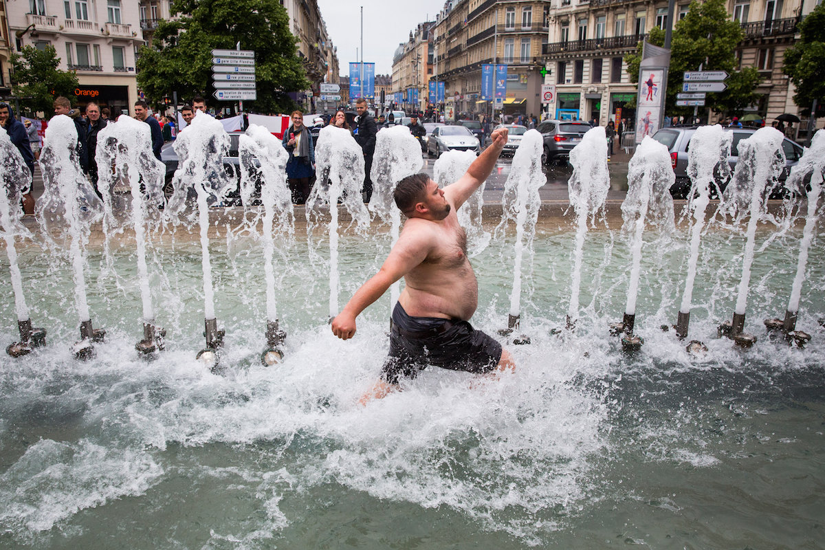 England fans jump in a fountain in Lille, France, ahead of the England-Wales game later today. 16 June 2016.