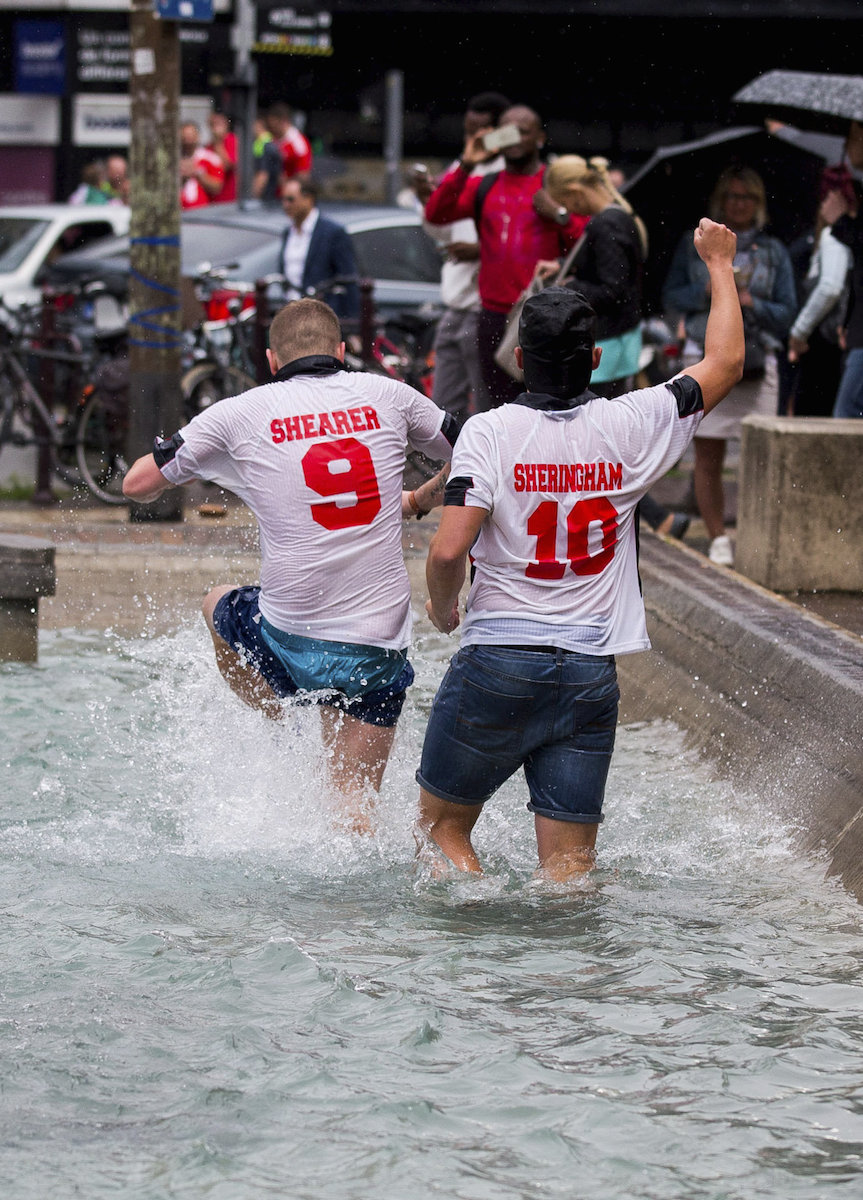 England fans wearing Shearer and Sheringham shirts jump in a fountain in Lille, France, ahead of the England-Wales game later today. 16 June 2016.